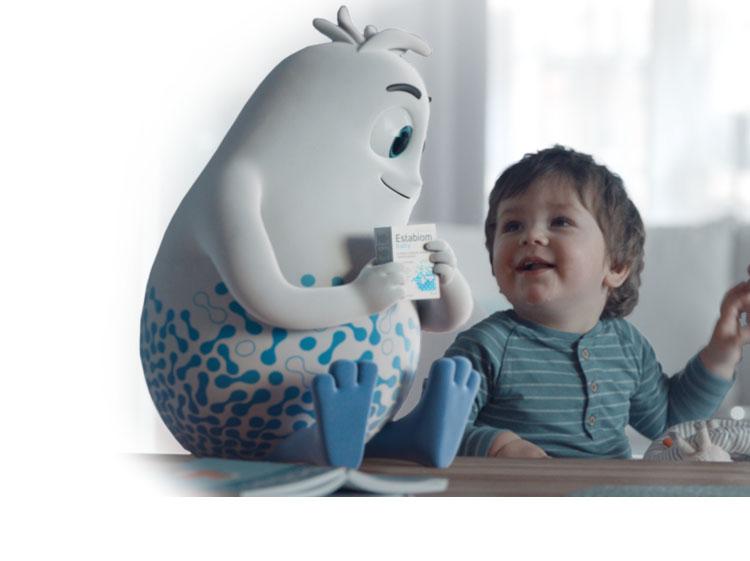 Biały ludzik Estabiom siedzi obok małego chłopczyka, trzymając w rękach opakowanie Estabiom Baby