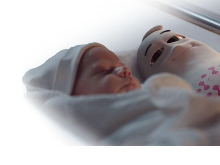 Biały ludzik Estabiom leży obok noworodka w szpitalu