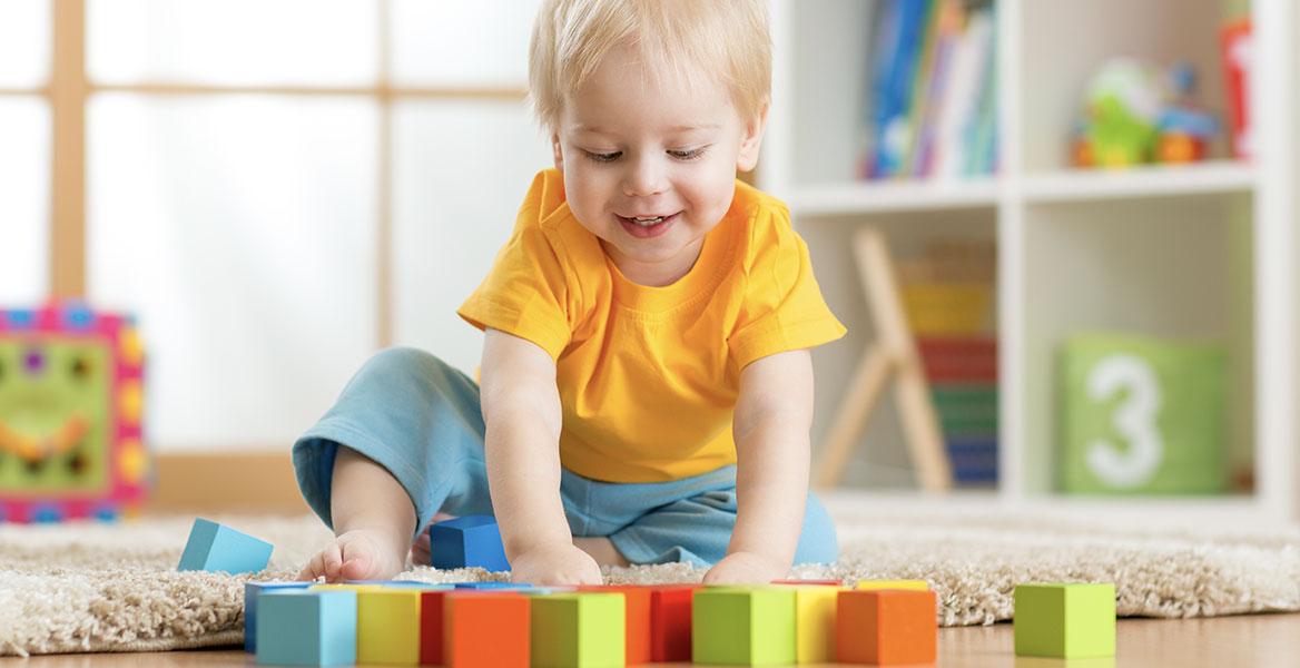 Jak bawić się z trzylatkiem? Mały chłopiec o blond włosach w kolorowym ubranku bawi się klockami na podłodze.