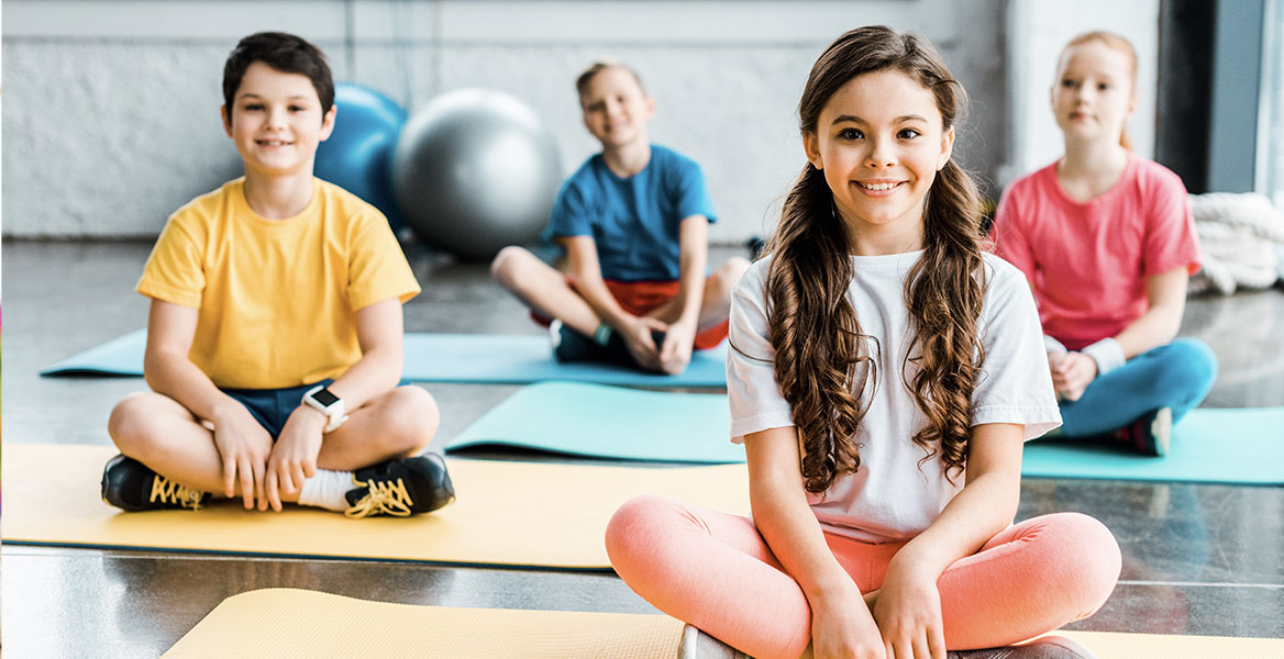 Jak wzmocnić odporność u dzieci? Co na odporność u dzieci sprawdzi się najlepiej? Dzieci siedzą na matach podczas zajęć z aktywności fizycznej.