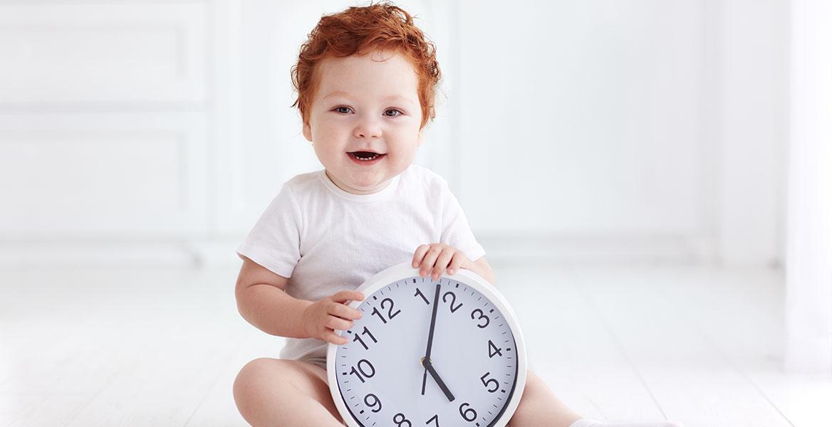 Nauka zegara - jak nauczyć dzieci odczytywać godzinę na zegarku? Mały rudy chłopczyk trzyma w rączkach zegar wskazówkowy.