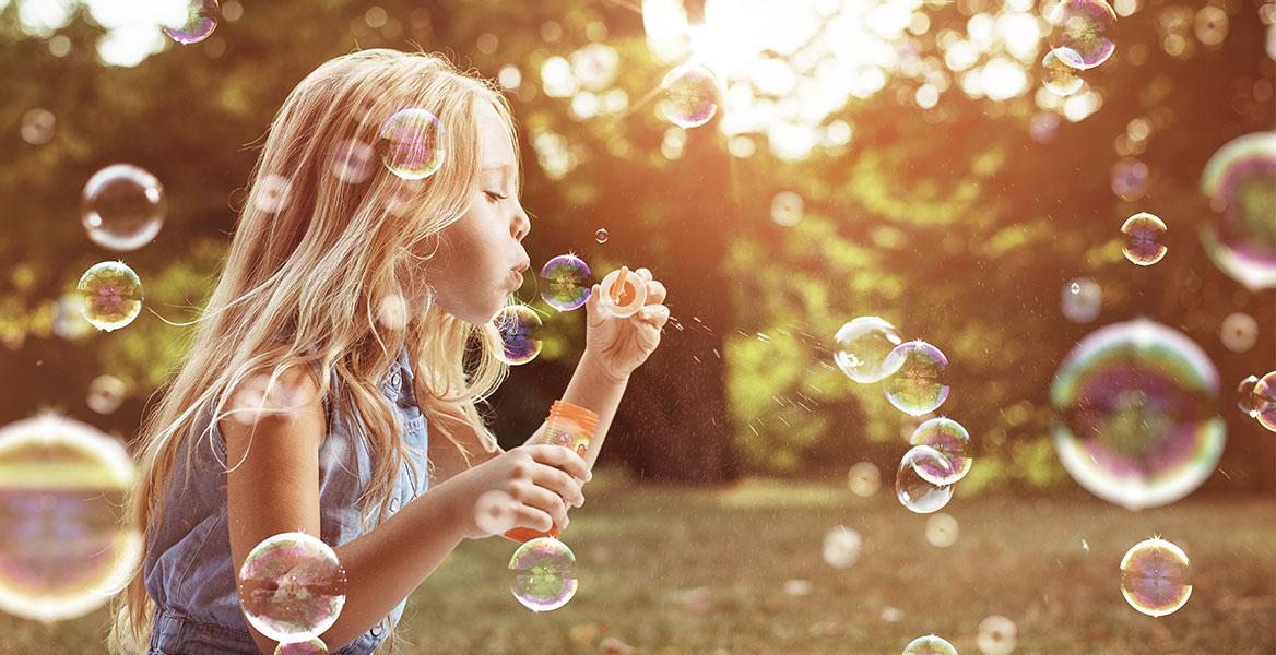 Stres u dzieci - jak sobie z nim poradzić? Dziewczynka puszcza bańki mydlane w letniej scenerii.