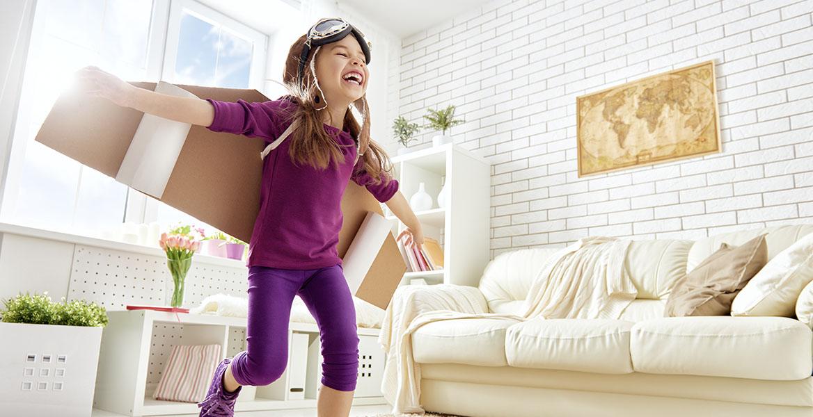 Zabawy dla dzieci w domu. Dziewczynka ze skrzydłami z kartonu na plecach bawi się w samolot.