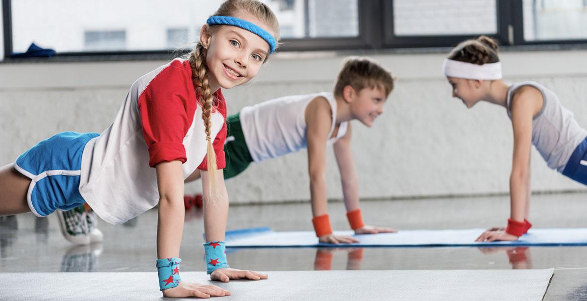 Ćwiczenia dla dzieci - jakie będą najlepsze dla dzieci w wieku szkolnym? Dzieci ćwiczą w sali gimnastycznej na lekcji W-F.