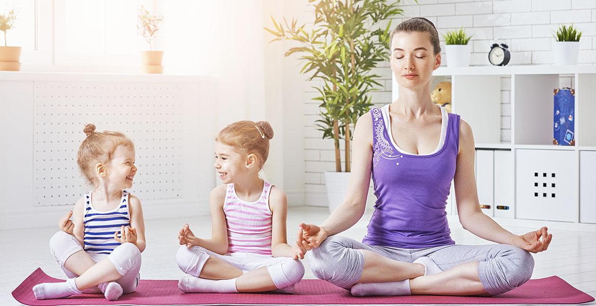 Ćwiczenia relaksacyjne dla dzieci. Mama z dwiema córeczkami medytuje na macie w salonie.