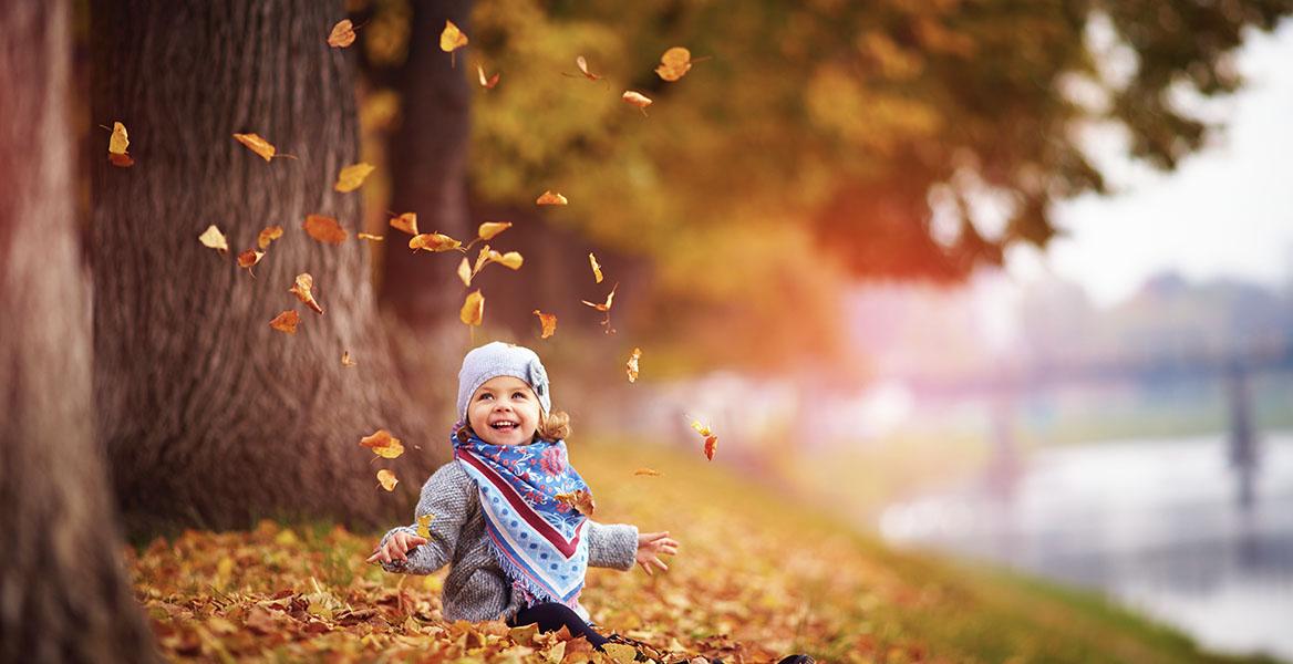 Odporność u dzieci - jak ją poprawić? Jak wzmocnić odporność u dzieci? Mała uśmiechnięta dziewczynka siedzi w jesiennych liściach.