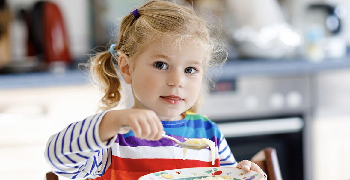 Probiotyk dla dzieci - dlaczego warto go stosować? Blondwłosa mała dziewczynka je owsiankę na śniadanie.
