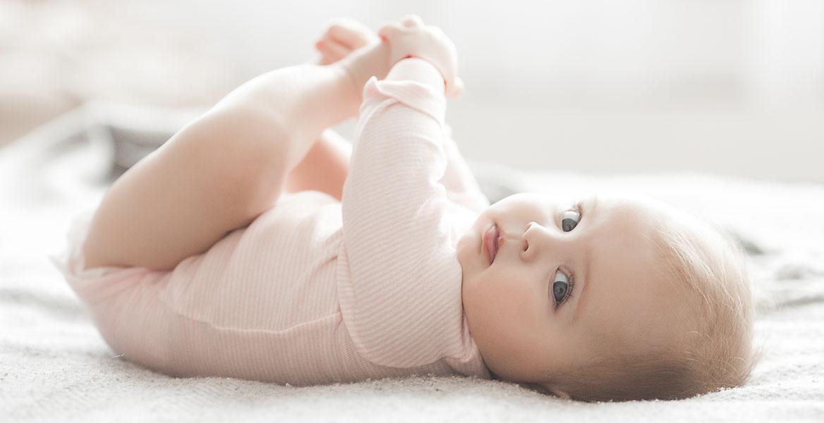 Probiotyki dla noworodków i niemowląt - kiedy rozpocząć suplementację u najmłodszych? Słodkie niemowlę w różowym body patrzy w obiektyw aparatu.