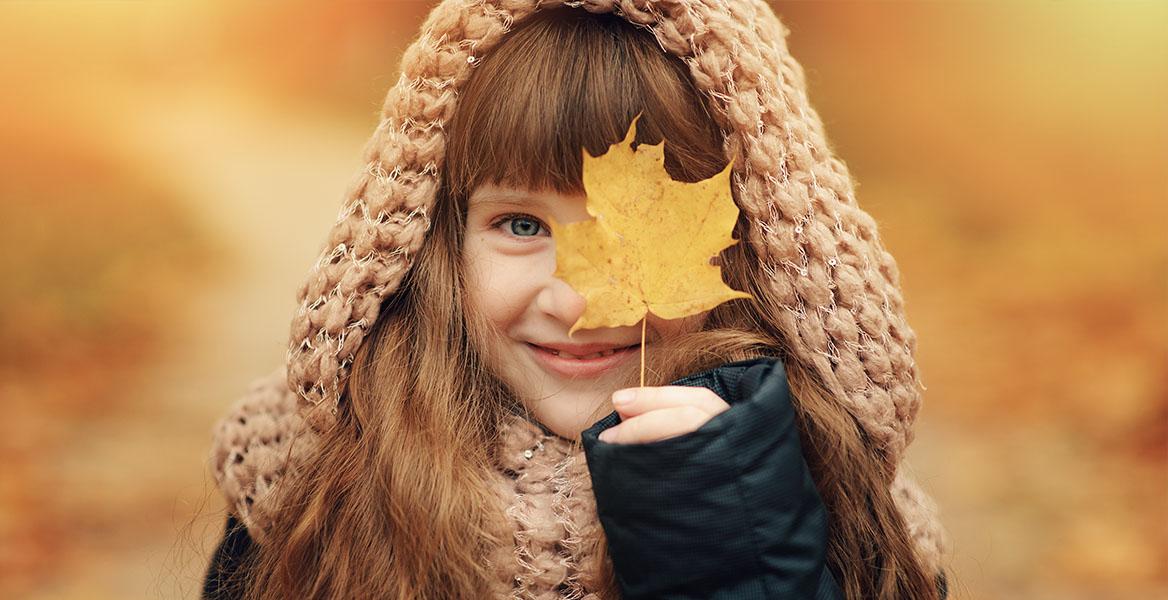 Witamina D dla dzieci – kiedy warto ją suplementować? Brązowowłosa dziewczynka uśmiecha się do aparatu zakrywając jedno oko jesiennym liściem.