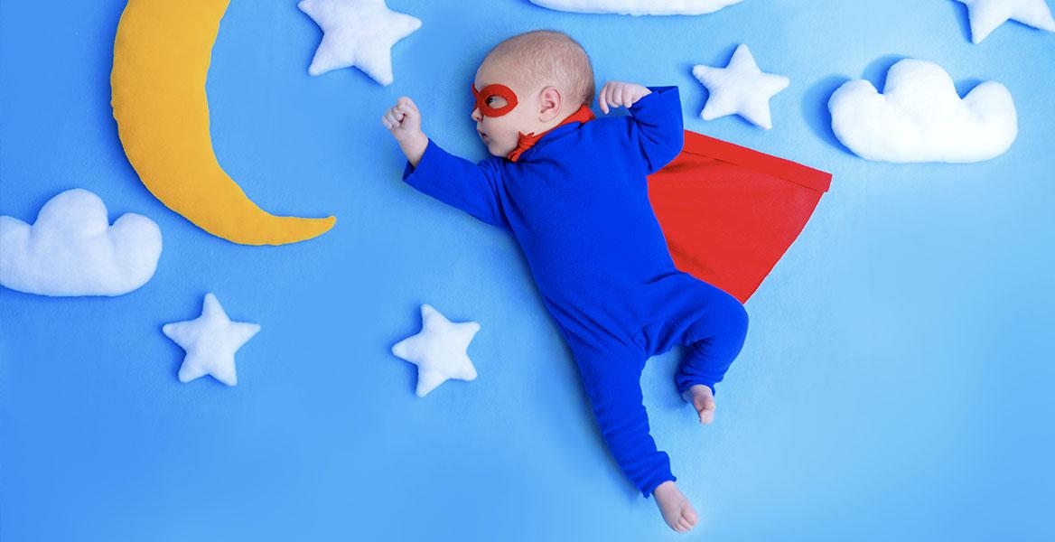 Witamina D dla niemowląt i noworodków - dlaczego warto ją stosować? Niemowlę przebrane za supermana śpi w otoczeniu pluszowego księżyca, gwiazdek i chmurek.