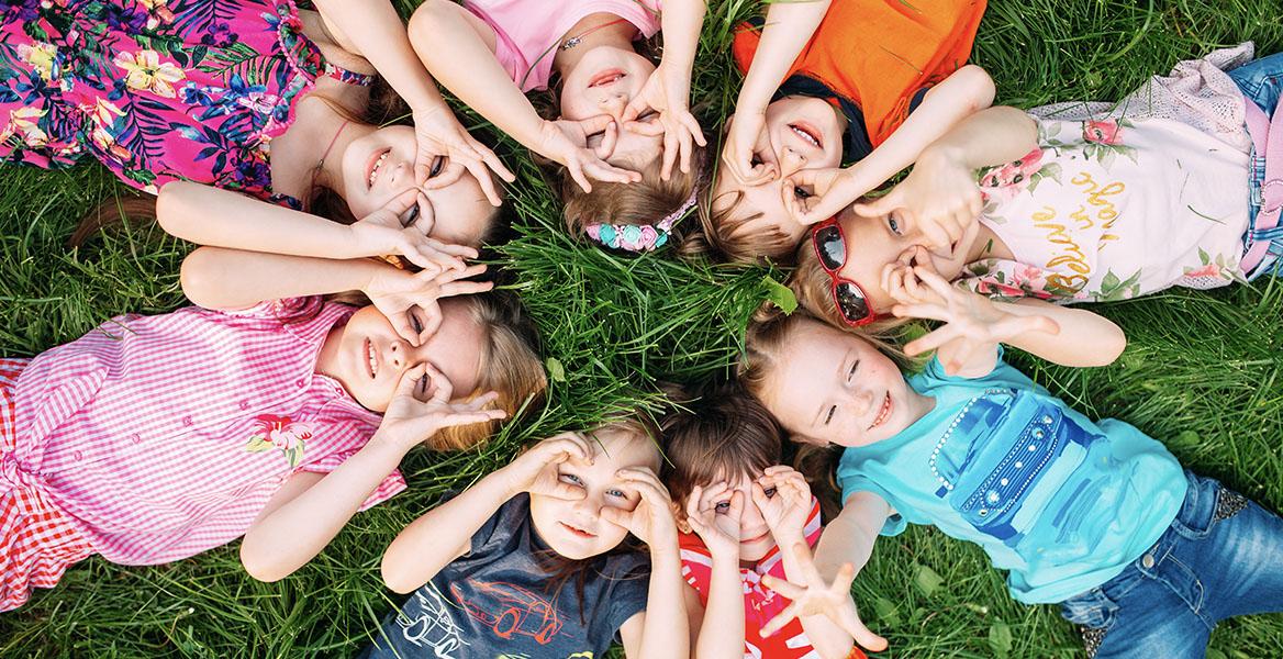 Witaminy na odporność dla dzieci. Dzieci leżą na zielonej trawie w kółku i przytykają palce do oczu jakby trzymały lornetkę.