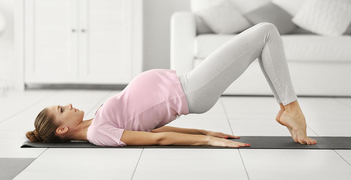 Ćwiczenia w ciąży - jak ćwiczyć bezpiecznie? Kobieta w ciąży ćwiczy w domu na macie w salonie.