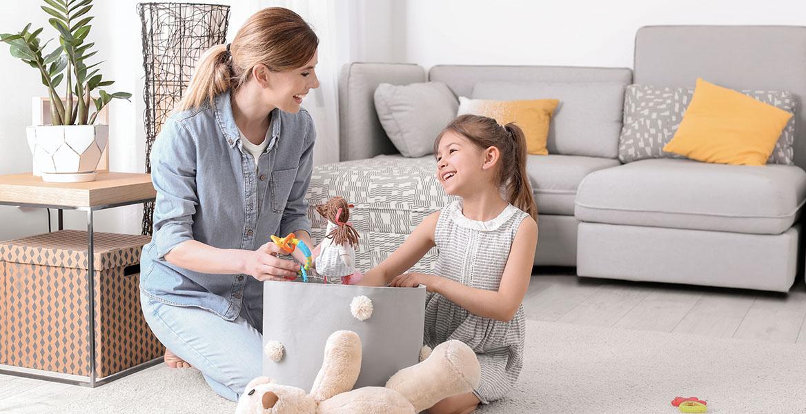 Jak nauczyć dziecko sprzątać? Nauka sprzątania. Mama uczy córeczkę, jak sprzątać po sobie zabawki.